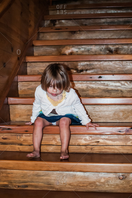 Little girl sitting on a wooden staircase