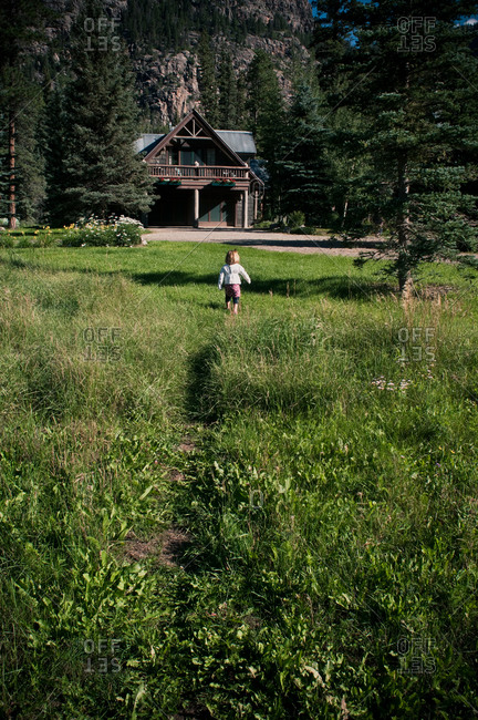 Little girl walking through a field toward a mountain lodge