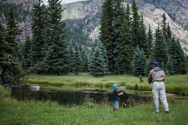 Boy watching his grandfather fish in a mountain pond