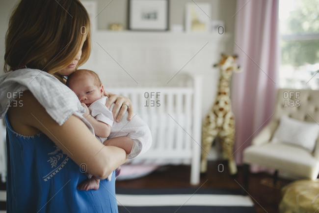 Mother patting newborn baby's back to burp it stock photo - OFFSET