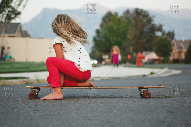 Little girl riding on a long board skateboard