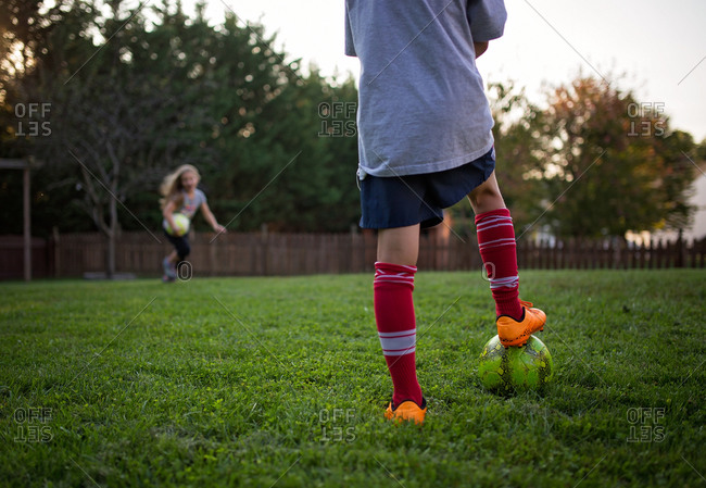 Kids playing soccer in their yard