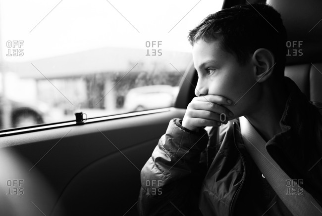 Portrait of a boy looking out the window of a car