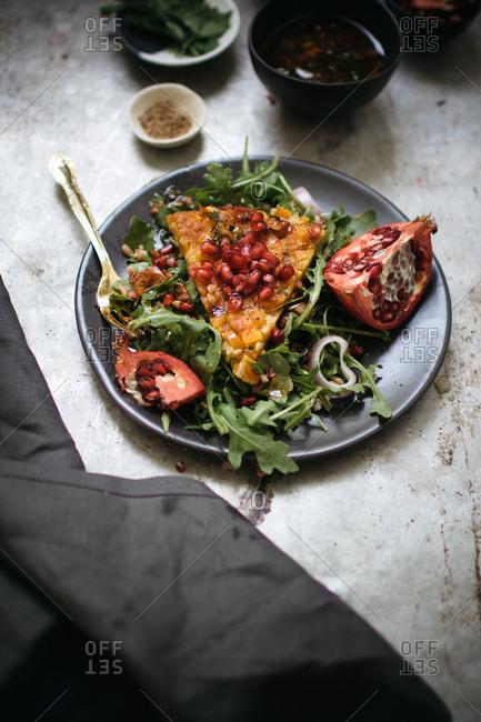 Butternut squash farinata with pomegranate and arugula salad