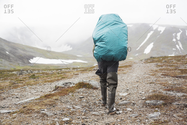 Man in waders carrying large blue tarp
