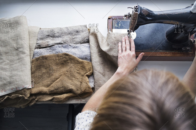 Woman sewing burlap on antique sewing machine