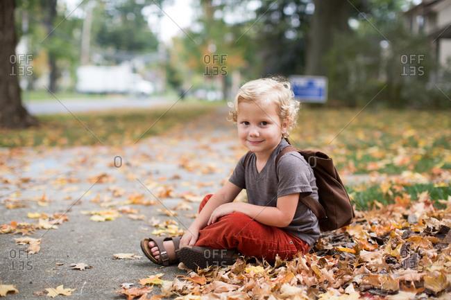 Little boy sitting on outside in autumn