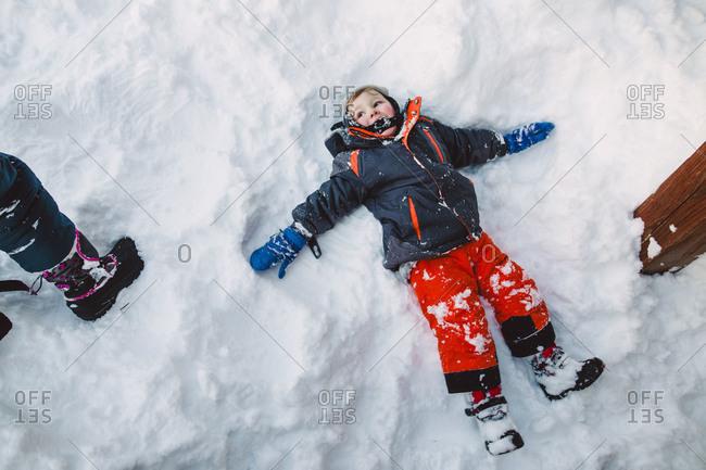 Little boy lying in the snow