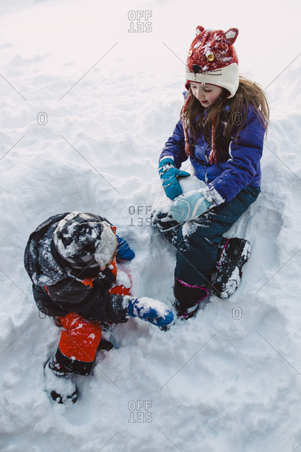 Two siblings making snowballs in the snow