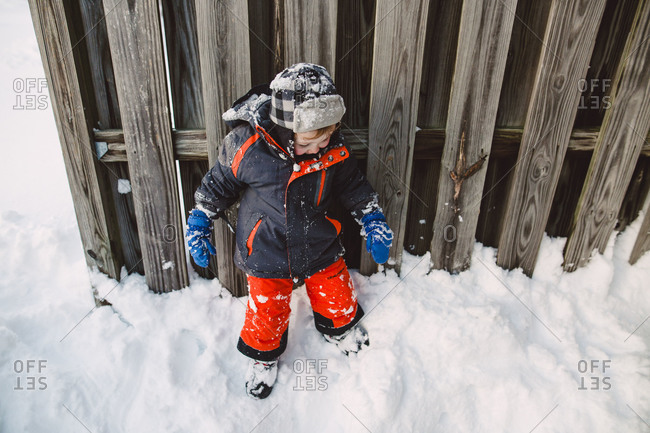 Little boy standing by a wooden fence in the winter