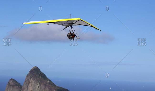 Rio De Janeiro, Brazil - September 9, 2010: A tandem hang glider flying above the hillside of Pedro Bonita, Rio De Janeiro, Brazil