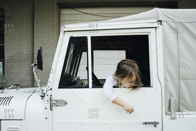 Little girl reaching to open door of a white truck