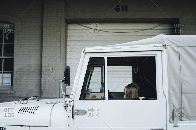 Little girl peeking out of a truck window