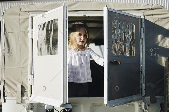 Little girl opening back doors on white truck