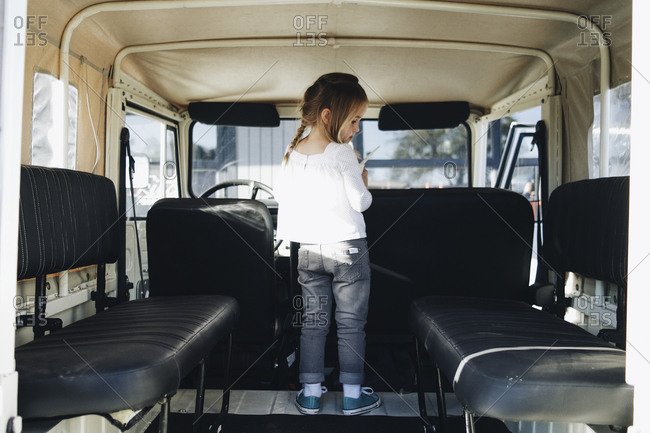 Little girl standing in the back of an SUV