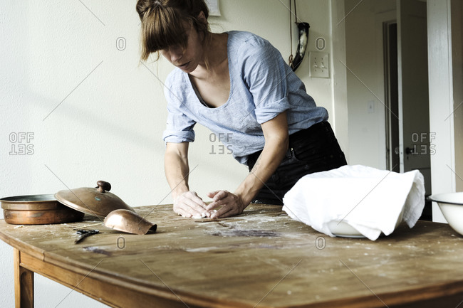 Woman kneading dough on a wooden table