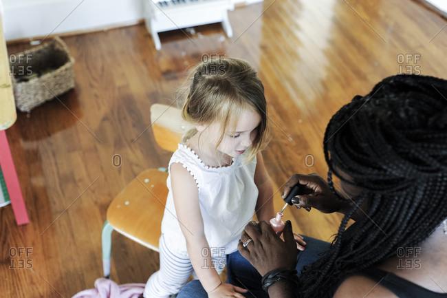 Woman putting fingernail polish on a little girl's nails