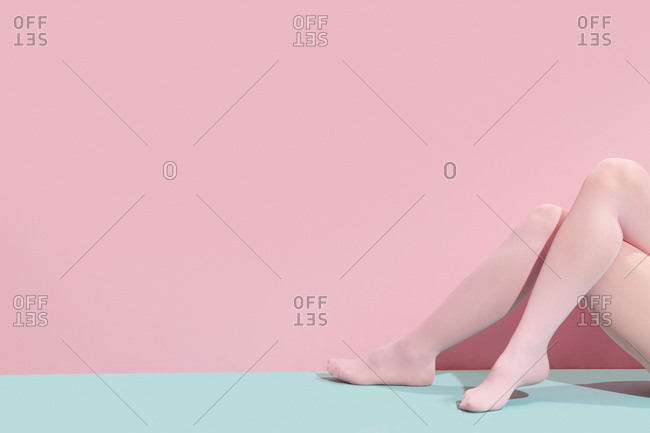 Legs of a woman wearing tights on blue and pink background