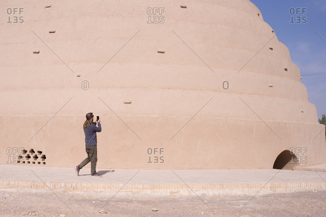 Tourist taking a photograph of a historical site in Iran
