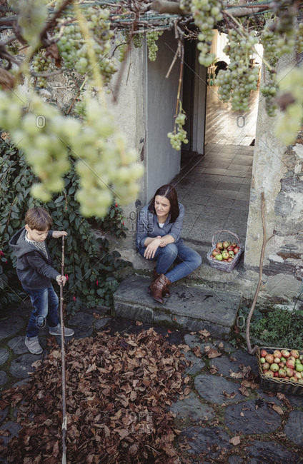 Woman sitting at entrance of country house watching her son picking autumn leaves
