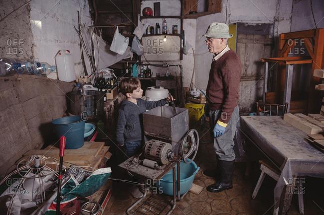 Senior man explaining his grandson something in his workshop