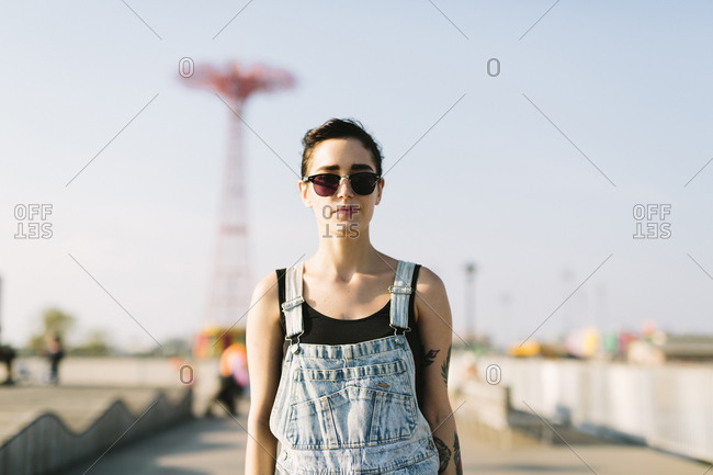 Young woman with fairground ride in the background, Coney Island, New York