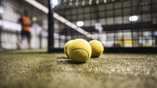 Paddle tennis balls in court with blurred player in background