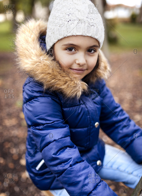 Portrait of little girl wearing blue jacket in autumn