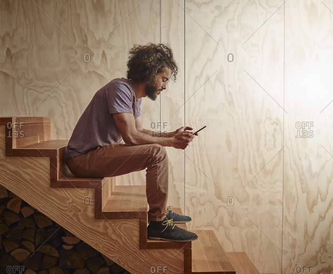 Young man sitting on wooden stairs looking at digital tablet