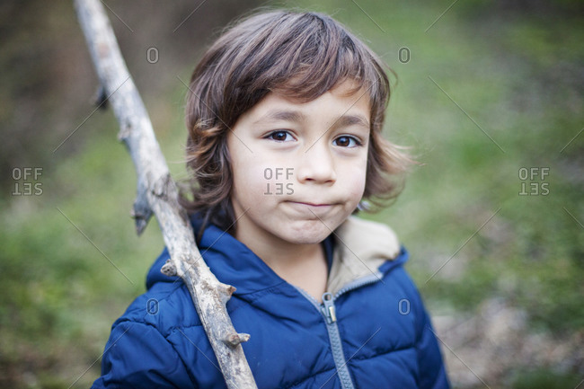 Portrait of little boy with a branch in nature