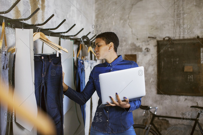 Fashion designer using a laptop and looking at jeans