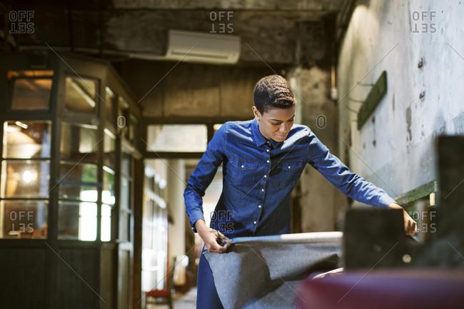 Fashion designer unrolling fabric
