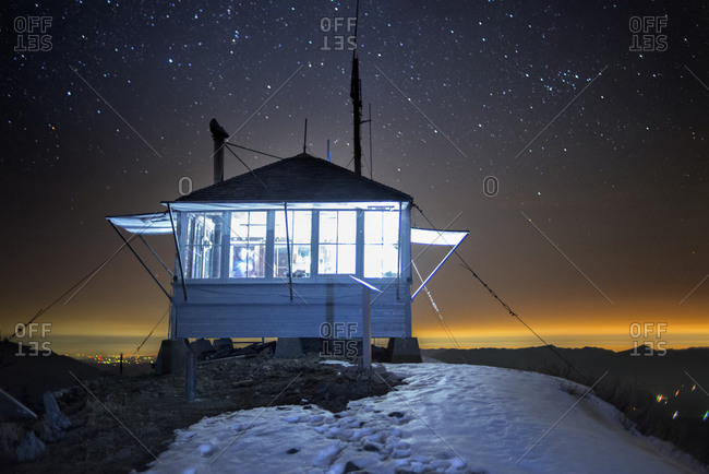 Illuminated lookout cabin under the night sky