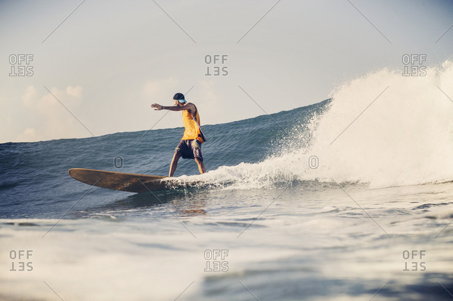 Young surfer wearing hat riding a big wave