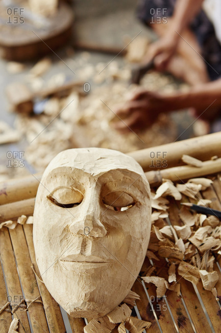 A traditional wooden mask being made in a carver's workshop