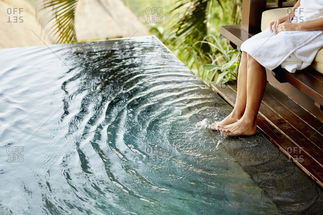 A person sitting on a bench with her feet in the pool making ripples