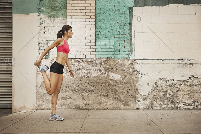Close up of a woman in running gear stretching her legs before a run