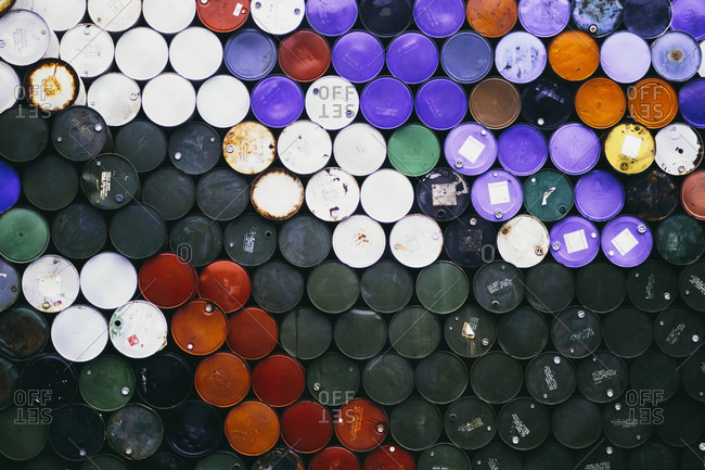 Large pile of colorful petroleum barrels stacked up