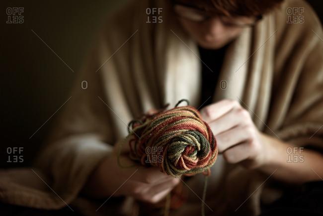 Boy in blanket untangles skein of yarn