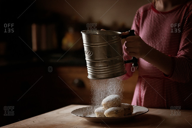 Girl sifting confectioners sugar on plate of muffins