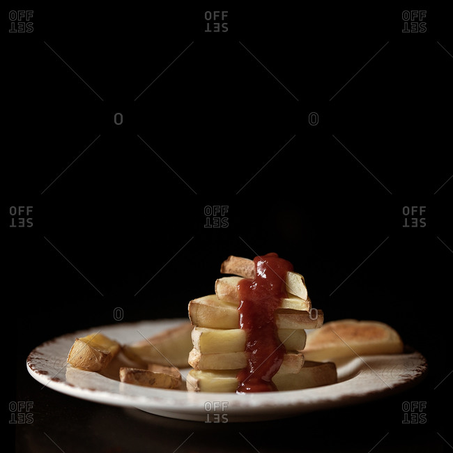 Plate of stacked homemade fries drizzled in ketchup