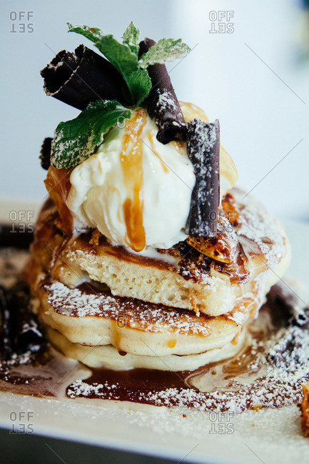 Stack of pancakes served with ice cream and curls of dark chocolate