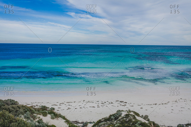 Calm tide at beautiful beach with reefs below aqua blue water