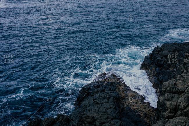 Waves crashing on black volcanic rocky coast