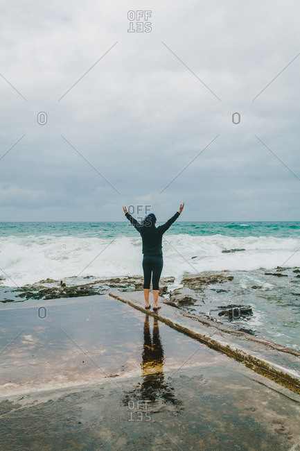 Back view of woman standing with arms raised at ocean