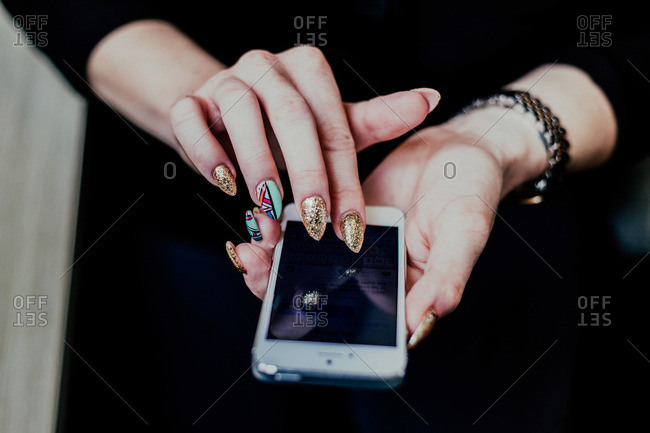 Close-up of woman's hands with funky manicure texting on smartphone
