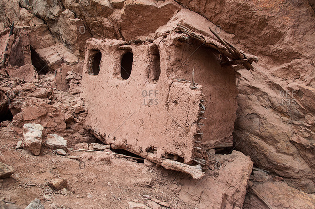 Ancient mud dwelling on hillside in desert landscape