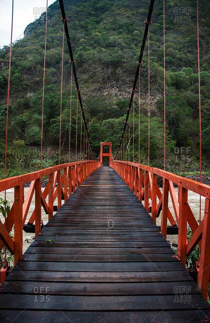 Orange suspension footbridge over river in wilderness