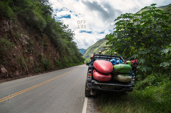 Truck packed with kayaks and river gear parked on road in wilderness