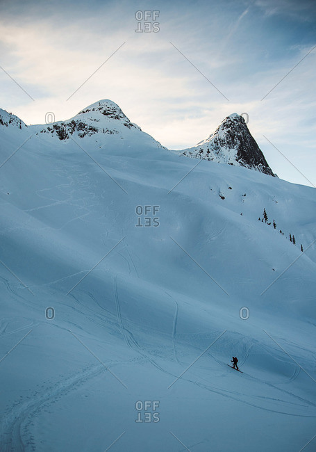 Backcountry skier on mountain covered with ski tracks